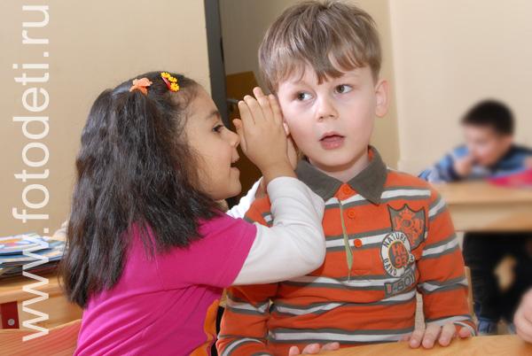 Девочка шепчет мальчику на ухо какие-то секреты.