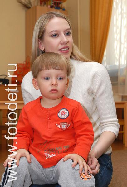 На фотографии малыш играет с мамой